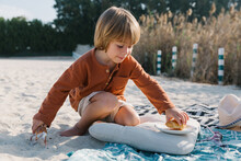 A Little Boy On The Beach Is Going To Eat A Croissant