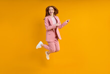 Successful Business Woman In Suit Jumping Pinting Index Finger At Side, Isolated On Yellow Background, Shopping. Portrait. Copy Space