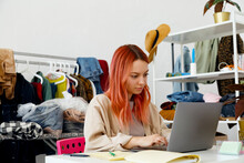 Female Entrepreneur Working With Laptop In Fashion Store