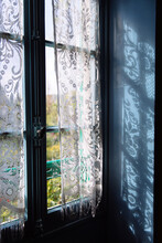 A Blue Window With A Lace Curtain