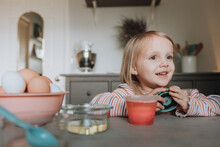 Young Girl Waiting For Egg To Dye With Timer