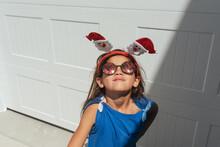 Girl Wearing A Santa Headband.