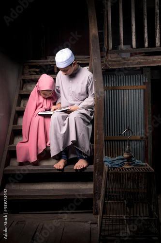 Obraz na plátně A brother and a cute little girl, an Asian Muslim, is practicing reading Quran with faith on the stairs in an old wooden house