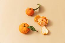 Peeled Leafy Oranges On Orange Background