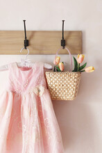 Little Pink Dress With Straw Purse Hanging On Hooks