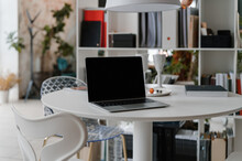 Netbook On White Table In Workspace