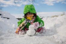 Young Girl Making Snowballs