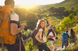 canvas print picture - Group of happy backpackers trekking on sunny day. Young tourists traveling and enjoying active summer vacation. Smiling woman looking at camera and waving hand walking down hiking trail with friends
