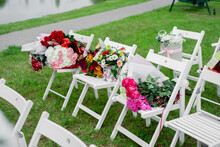 Bouquets Of Flowers On Wooden White Chairs At The Exit Ceremony