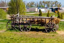 Old Wooden Cart With Hay At Farmyard