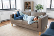 Leinwandbild Motiv people, boredom and depression concept - bored or lazy young man lying on sofa at home
