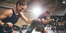 Man And Woman Hardly Exercising At Gym