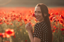Young Brunette Woman 25-30 Years Old With Long Groomed Hair In Black Dress White Polka Dots Enjoy A Poppy Flowers In Field