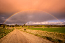 A Ground Level View Looking Down A Dirt Road With A Vivid Rainbow Arching Overhead