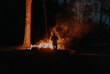 Silhouette Of Man Standing At Fire