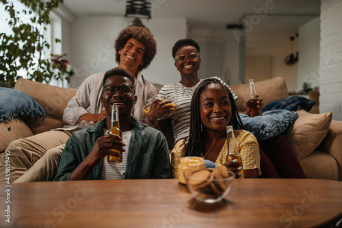 Fotografia Friends drinking beer and having fun in the living room