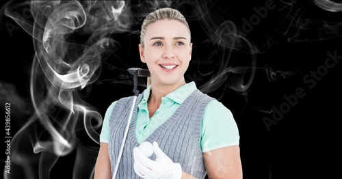 Caucasian female golf player holding golf club and ball against smoke effect on black background