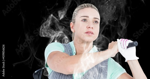 Close up of caucasian female golf player swinging golf club against smoke effect on black background