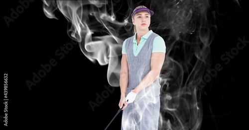 Caucasian female golf player holding golf club against smoke effect on black background