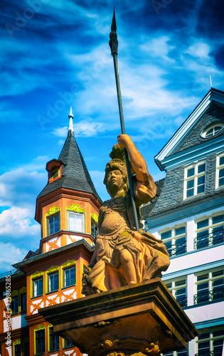 Fototapeta Minerva fountain in front of a beautiful half-timbered facade on the Römerberg