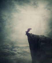 Surreal Scene With An Angel Fallen In Limbo, Sitting Alone On The Edge Of A Cliff Between The Skies. Magical Winged Creature Expelled From Paradise. Metaphorical And Conceptual Imaginary World View