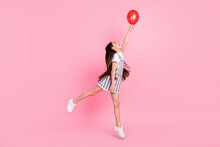 Full Size Photo Of Attractive Nice Happy Little Girl Jump Up Catch Hand Look Balloon Isolated On Pink Color Background