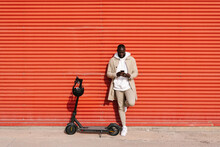 African Leaning On A Wall Next To His Scooter