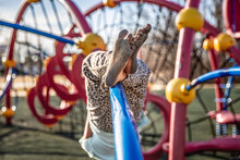 Girl With Dirty Bare Feet Hanging Upside Down At The Playground