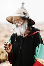 Happy Hippie Rastaman Smoking Cannabis On Field