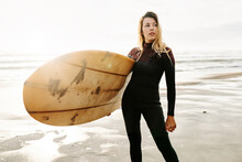 Female Surfer Standing At The Beach With Surfboard