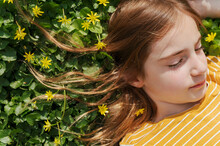 Little Girl Relaxing Among Yellow Flowers, Hair Strewn In The Clover