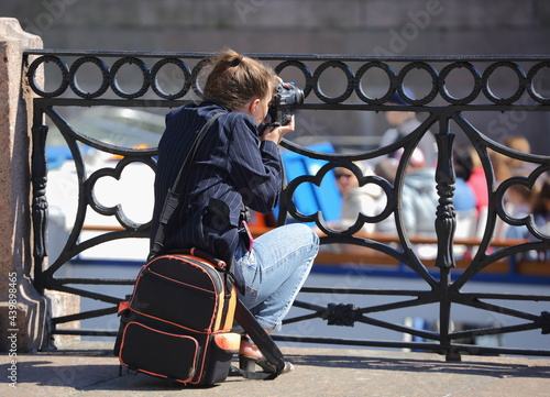 Fotografiet Photographer girl at the river embankment fence, Moika River Embankment, Saint P