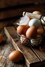 Chicken Eggs With Feathers In A Basket On Rustic Background. Rustic Style