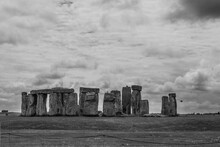 Black And White Photo Of The Mystical Stones Of Stonehenge On A Cloudy Day With Crows Sitting On The Stones