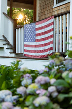 American Flag Hanging On Porch With Hydrangea Flowers