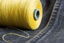 Close-up Of A Spool Of Yellow Thread On Dark Grey Denim With Stitch.