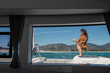 Woman Reading Book On Deck Of Yacht