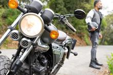 Man With Helmet In Hand Standing Near Parked Motorbike