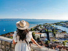 Rear View Of Woman Standing On Viewpoint Above Seaside Town Of Omiš In Croatia During Summer Holiday