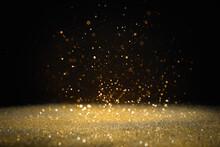 Shiny Golden Glitter Falling Down On Black Background. Bokeh Effect