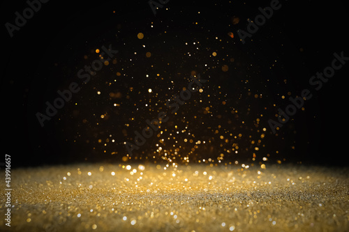 Shiny golden glitter falling down on black background Fototapet