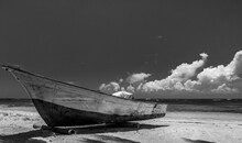 Dramatic High Contrast Black And White Image Of A Old Weathered Wooden Fishing Boat Abandoned On The Caribbean Coast In The Dominican Republic. With White Sand And Cloudy Skies.