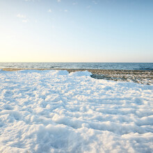 Frozen Baltic Sea Shore On A Clear Day, Snow Texture Close-up. Blue Sky. Picturesque Winter Scenery. Seasons, Nature, Ecology, Environment, Climate Change, Global Warming. Panoramic View, Copy Space