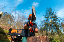 Lumberman In Safety Equipment Chopping Wooden Logs With Axe