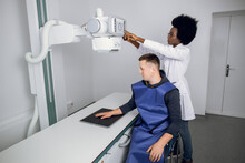 Classic Ceiling-mounted X-ray System. Young African Woman Doctor Radiologist And Male Caucasian Patient In X-ray Room, During X-ray Of Human Hand. Xray Diagnostics Of Bone Fracture