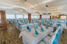 Empty Restaurant With Tables Covered By White And Blue Tableware Ready For The Ceremony