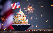 Cupcake And American Flag. Sparklers Or Fireworks Lights Burning In A Cake. 4th Of July, Independence, Presidents Day. Tasty Cupcakes With White Cream Icing And Colored Stars Sprinkles. Sweet Dessert.