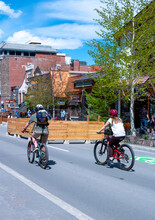 Banff Village Street With Bikers Riding Down Town COVID-19 Sign