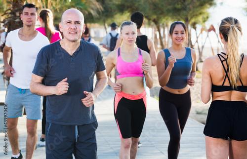 Canvastavla Sporty women and men running along embankment in sunny morning
