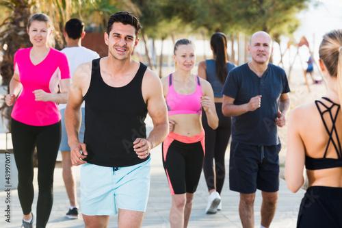 Fotografiet Sporty women and men running along embankment in sunny morning